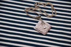 Etnika. Marine jewellery necklace on striped fabric with small key. Handmade white pendant of polymer clay royalty free stock photo