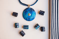 Etnika. Marine jewellery pendant and beads isolated and striped fabric. Handmade blue necklace from polymer clay stock image