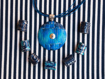 Etnika. Marine jewellery pendant and beads on striped fabric. Handmade blue necklace from polymer clay royalty free stock photos
