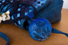 Etnika. Marine jewellery pendant with small blue bag and white flowers. Handmade pendant of polymer clay stock image