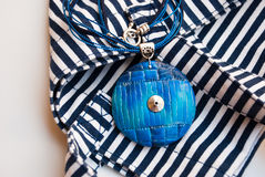 Etnika. Marine jewellery pendant on striped fabric. Handmade blue necklace from polymer clay royalty free stock image