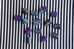 Etnika. Marine and purple jewellery beads on striped fabric. Handmade blueand violet beads from polymer clay stock image