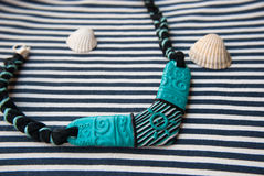 Etnika. Marine summer necklace on striped fabric. Handmade jewelry of polymer clay. Ethnic style royalty free stock photo