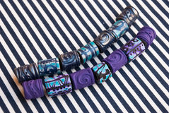 Etnika. Marine and violet jewelry beads on striped fabric. Handmade beads from polymer clay royalty free stock photography