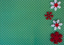 Etnika. New year background with red  snowflakes on green paper with white points. Christmas card idea.Space for text.Xmas blank Stock Photos