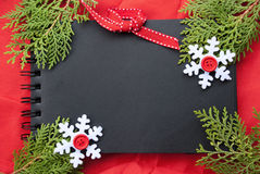 Etnika. New Year handmade frame. Black notebook on red fabric with snowflakes and pine brunches. Space for text, place for message.Christmas background Stock Images