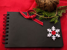 Etnika. New Year handmade frame. Black notebook , snowflakes and pine brunch. Space for text, place for message Royalty Free Stock Photo
