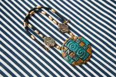 Etnika. Pendant egypt style on striped fabric. Handmade jewelry of polymer clay. Jewelry background Royalty Free Stock Photo
