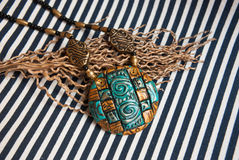 Etnika. Pendant egypt style on striped fabric. Handmade jewelry of polymer clay. Jewelry background.Bohemian necklace Stock Images