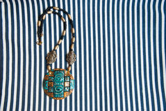 Etnika. Pendant egypt style on striped fabric. Handmade jewelry of polymer clay. Jewelry background.Bohemian necklace. Space for text Stock Photos