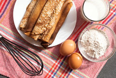 Etnika. Russian style crepes with glass of milk, whisk, flour and eggs.Food background stock photo