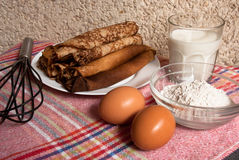 Etnika. Russian style crepes with glass of milk, whisk, flour and eggs.Food background stock photography