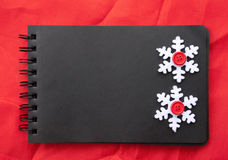 Etnika. Simple New Year handmade frame. Black notebook , snowflakes on red fabric. Space for text, place for message Royalty Free Stock Image