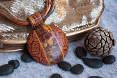 Etnika. Still life with boho orange pendant, golden bagand cone. Hamdmade jewelry of polymer clay royalty free stock images