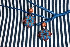 Etnika. Still life with brown earrings and blue brunch on striped fabric. Handmade jewelry of polymer clay. Unique design stock photos