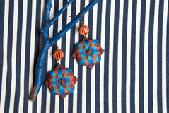 Etnika. Still life with brown earrings and blue brunch on striped fabric. Handmade jewelry of polymer clay. Unique design royalty free stock photography