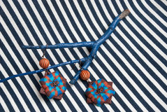 Etnika. Still life with brown earrings and blue brunch on striped fabric. Handmade jewelry of polymer clay. Unique design.Fashion earrings royalty free stock photos