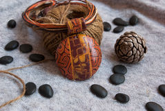 Etnika. Still life with Orange jewelry pendant, decorative cord and small black stones. Handmade jewelry of polymer clay royalty free stock images