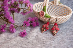 Etnika. Still life of pink earrings with beautiful flowers and ceramic vase. Handmade earrings of polymer clay royalty free stock images