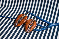 Etnika. Still life with terracota earrings and blue brunch on striped fabric. Handmade jewelry of polymer clay. Unique design royalty free stock image