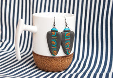 Etnika. Still life with white cup and african earrings on striped fabric. Handmade jewelry of polymer clay royalty free stock images