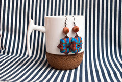 Etnika. Still life with white cup and ethnic earrings on striped fabric. Handmade jewelry of polymer clay. New idea for show jewelry royalty free stock images