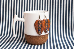 Etnika. Still life with white cup and terracota earrings on striped fabric. Handmade jewelry of polymer clay. New idea for show jewelry royalty free stock photo