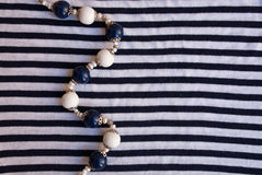 Etnika. String of elegant beads in marine style on striped fabric. Handmade jewelry necklace of polymer clay royalty free stock images
