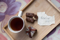 Etnika. Surprise breakfast with note of apology. Top view with cup of tea, chocolate bars, small present box and note of apology stock images
