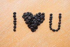 Etnika. Text I love you from small black sea stones on woodden table. Top view royalty free stock images