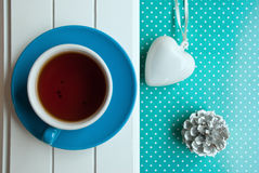 Etnika. Top view blue cup with tea on white wodden desk and green background with points heart and pine Royalty Free Stock Photo