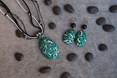 Etnika. Top view of jewelry set pendant and earrings with black stones on grey fabric. Handmade jewelry of polymer clay royalty free stock image