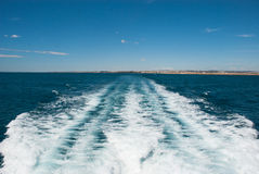Etnika. Trail from the boat on the Mediterranean sea with small line of Spain coast stock photos