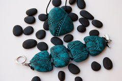 Etnika. Turquoise jewelry set pendant and bracelet with black stones on white background. Marine jewellery. Handmade jewelry of polymer clay royalty free stock images