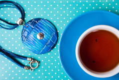 Etnika. Unexpected morning gift necklace from polymer clay and cup of tea. Handmade jewelry. Top view Royalty Free Stock Photography