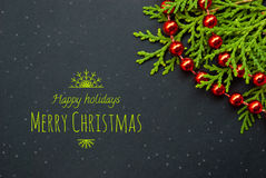 Etnika. Unique Christmas or New Year card. Black paper board closeup with pine brunch and red garland and text merry christmas in green color.  Frame image for Royalty Free Stock Photography