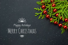 Etnika. Unique Christmas or New Year card. Black paper board closeup with pine brunch and red garland and text merry christmas.  Frame image for seasonal Royalty Free Stock Photography