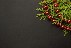 Etnika. Unique Christmas or New Year photo background. Black paper board closeup with pine brunch and red garland.  Frame image for seasonal greeting card Stock Image