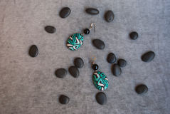 Etnika. Unique earrings jewelry emerald color with small black stones on grey fabric. Top view.Handmade jewelry of polymer clay stock image