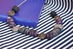 Etnika. Unique jewelry beads with violet book on striped fabric. Polymer clay jewelry.Bohemian style. Handmade work stock photo