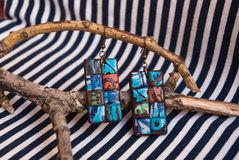 Etnika. Unique jewelry earrings on branch of tree. Handmade jewelry of polymer clay. Ethnic style. African motifs royalty free stock photo