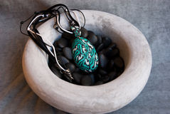 Etnika. Unique pendant in big ceramic bowl. Still life.Handmade jewelry of polymer clay stock photography
