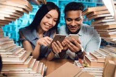 Etnisch Aziatisch meisje en Indische gemengde die raskerel door boeken in bibliotheek wordt omringd De studenten gebruiken telefo stock foto