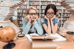 Etnisch Aziatisch meisje en wit die meisje door boeken in bibliotheek wordt omringd De studenten lezen boek stock afbeeldingen