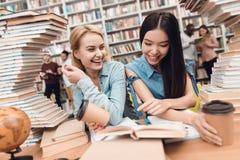Etnisch Aziatisch meisje en wit die meisje door boeken in bibliotheek wordt omringd De studenten lezen boek stock foto