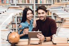Etnisch Aziatisch meisje en witte die kerel door boeken in bibliotheek wordt omringd De studenten gebruiken tablet stock foto's