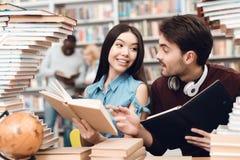 Etnisch Aziatisch meisje en witte die kerel door boeken in bibliotheek wordt omringd De studenten lezen boeken royalty-vrije stock foto