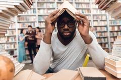 Etnische Afrikaanse Amerikaanse die kerel door boeken in bibliotheek wordt omringd De student is bored en vermoeid royalty-vrije stock afbeeldingen