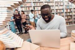 Etnische Afrikaanse Amerikaanse die kerel door boeken in bibliotheek wordt omringd De student gebruikt laptop stock foto