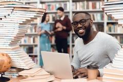 Etnische Afrikaanse Amerikaanse die kerel door boeken in bibliotheek wordt omringd De student gebruikt laptop en drinkt koffie stock afbeelding